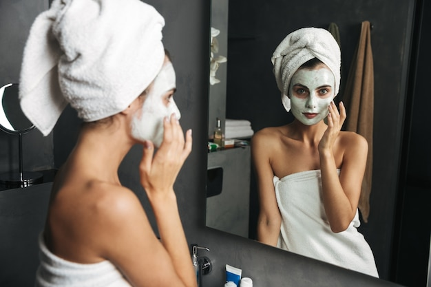 Zdjęcie młodej kobiety zawiniętej w ręcznik stosując maskę w łazience w pobliżu lustra
