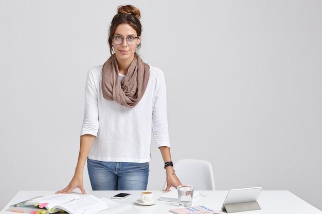 Zdjęcie młodej nauczycielki w stylowym stroju, przygotowuje się do seminarium lub lekcji, studiuje różne źródła literackie, pije latte, używa tabletu do wyszukiwania informacji w internecie, na białym tle na białej ścianie