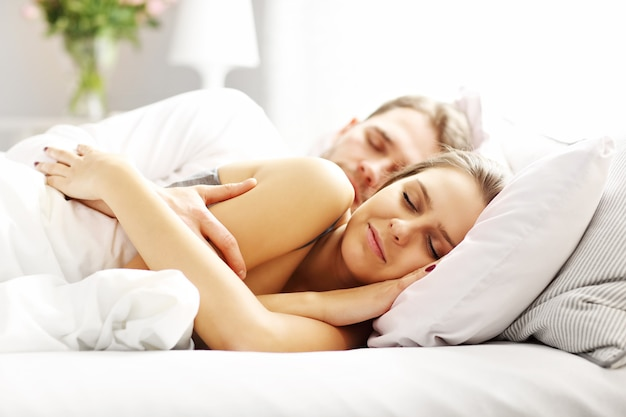 Zdjęcie młodej pary śpiącej w łóżku