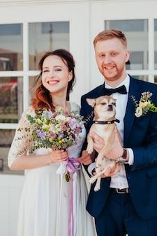 Zdjęcie młodej pary w dniu ślubu z psem
