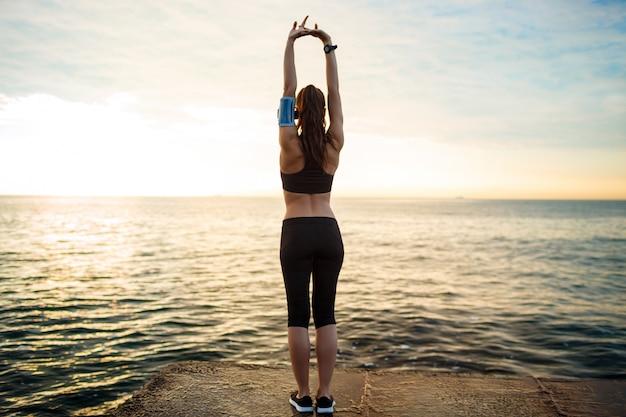 Zdjęcie młodej pięknej dziewczyny fitness sprawia, że ćwiczenia sportowe z morzem