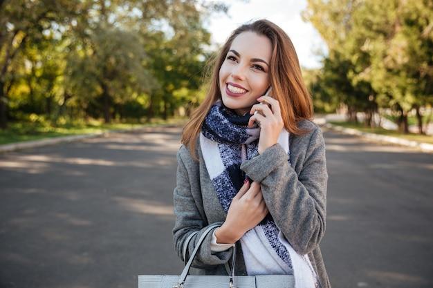 Zdjęcie młodej pięknej kobiety uśmiechnięta rozmawia przez telefon spójrz na bok.