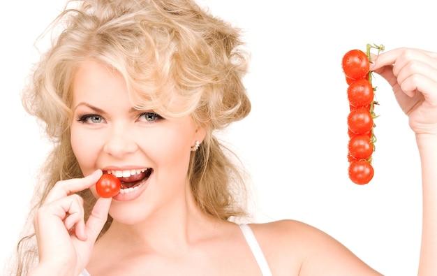 Zdjęcie młodej pięknej kobiety z dojrzałymi pomidorami