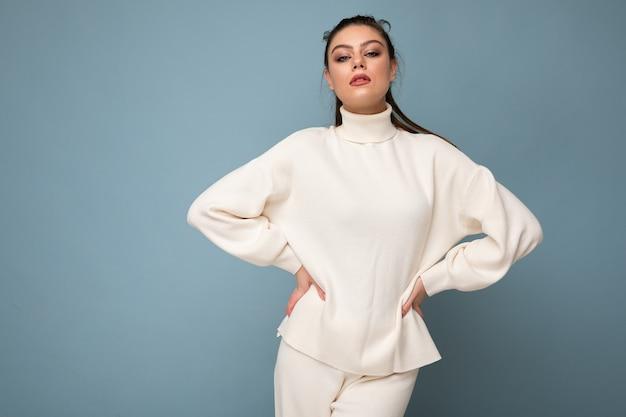 Zdjęcie młodej pięknej pewnej siebie seksownej stylowej brunetki kobiety na sobie dorywczo biały sweter