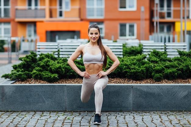 Zdjęcie młodej pięknej sportsmenki plenerowej ćwiczeń w mieście.