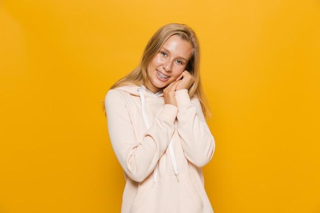 Zdjęcie młodej studentki lub uczennicy z aparatami ortodontycznymi uśmiecha się do kamery, odizolowane na żółtym tle