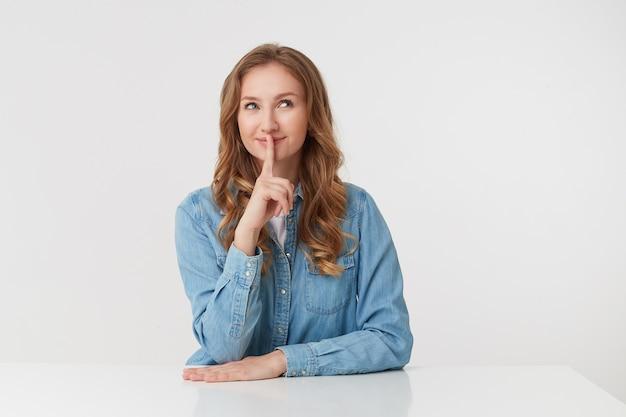 Zdjęcie młodej tajemniczej uroczej blondynki w dżinsowych koszulach, siedzącej przy białym stole, uśmiechającej się i pokazującej gest ciszy, proszę zachować spokój. stoi na białym tle.
