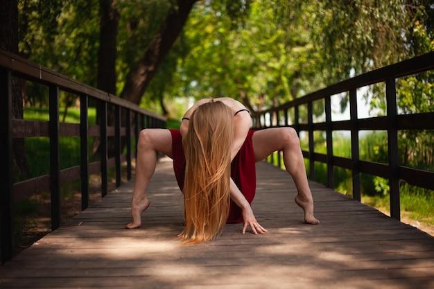 Zdjęcie młodej tancerki brzucha w parku. młoda blondynka tańczy na łonie natury. dziewczyna gimnastyczka w czerwonej spódnicy.