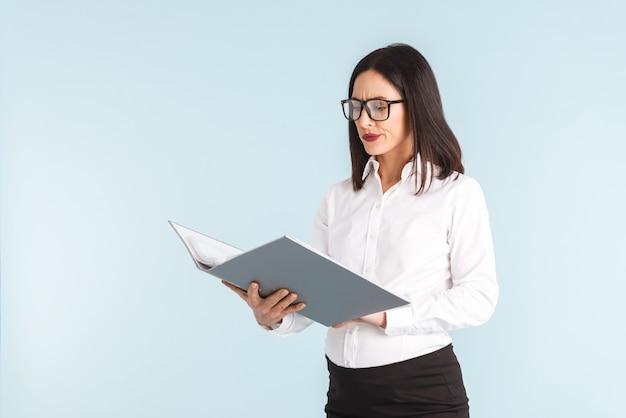 Zdjęcie młodej zdezorientowanej emocjonalnej kobiety w ciąży biznes na białym tle folderu.