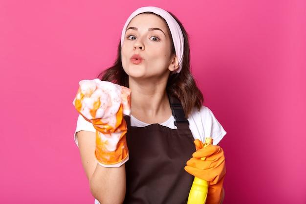 Zdjęcie młodych o przyjemnym wyrazie twarzy, nosi koszulkę i fartuch, wygląda na szczęśliwego, wykonując prace domowe, trzymając spray i wydmuchując piankę z gąbki. koncepcja higieny, sprzątania i czystości.