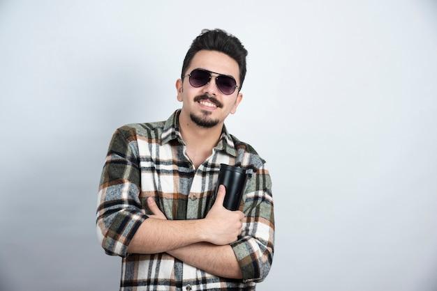 Zdjęcie młodzieńca w okularach pokazano czarny kubek na białej ścianie.