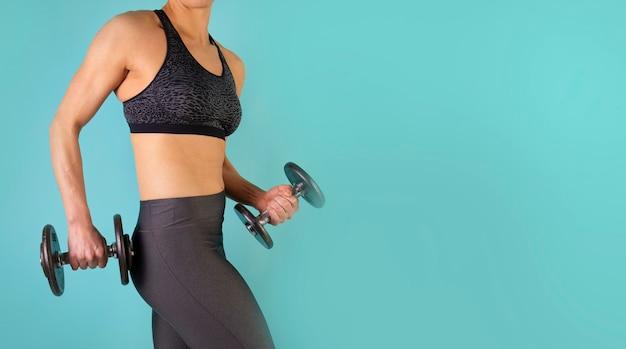 Zdjęcie modelu fitness mięśni pracy z hantlami na niebieskim tle. wysportowana kobieta robi ćwiczenia na ramiona. siła i motywacja, sport i zdrowy tryb życia. wolne miejsce na tekst lub logo