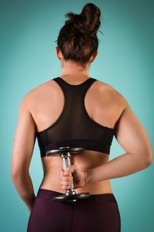 Zdjęcie modelu fitness mięśni pracy z hantlami na niebieskim tle. wysportowana kobieta robi ćwiczenia na ramiona. siła i motywacja, sport i zdrowy tryb życia.