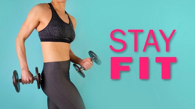Zdjęcie modelu fitness mięśni pracy z hantlami na niebieskim tle z tekstem. wysportowana kobieta robi ćwiczenia na ramiona. siła i motywacja, sport i zdrowy tryb życia. zachować sprawność.