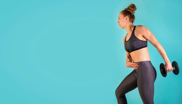 Zdjęcie modelu fitness mięśni pracy z hantle na niebieskim tle. wysportowana kobieta robi ćwiczenia na ramiona. siła i motywacja, sport i zdrowy tryb życia. wolne miejsce na tekst.
