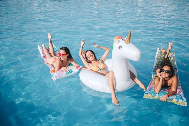 Zdjęcie modelu siedzi i leży na pływakach w basenie. oni odpoczywają. dwie kobiety leżące na brzuchu i pokazują swoje piękne ciała. model w środku wyciąga ręce do góry i uśmiecha się