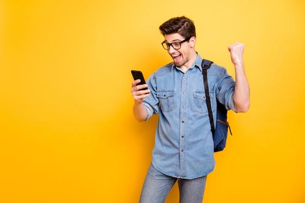 Zdjęcie modnego, wesołego, modnego, stylowego nerda, widzącego, jak jego egzaminy zostały zdane z doskonałym martwym dżinsem w dżinsach izolowane żywy kolor ściana