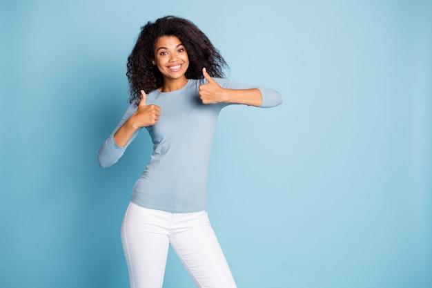 Zdjęcie modnej wesołej pozytywnej ładnej ładnej dziewczyny pozostawiającej pozytywne opinie na temat zakupionych towarów, uśmiechniętej, ząbkowanej, pokazującej kciuki do góry na białym tle w pastelowym niebieskim kolorze