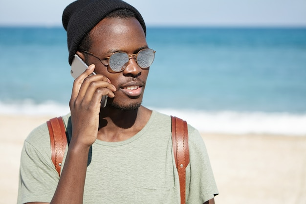 Zdjęcie modnie wyglądającego czarnego turysty płci męskiej z plecakiem, noszącego kapelusz i okulary przeciwsłoneczne przy słonecznej pogodzie, rozmawiającego przez telefon komórkowy