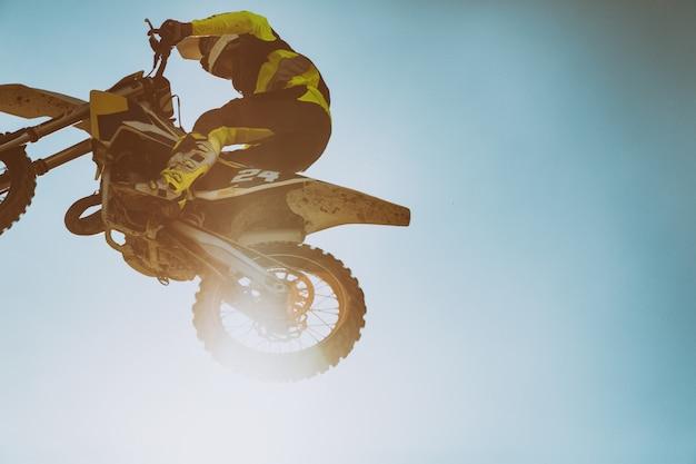 Zdjęcie motocyklisty wykonującego wyczyn kaskaderski i wyskakującego w powietrze
