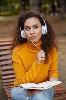 Zdjęcie myślącej pięknej młodej kobiety kręcone siedzieć na ławce w parku na zewnątrz, słuchając muzyki ze słuchawkami, pisząc notatki w notesie.