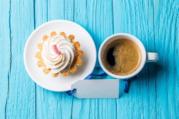 Zdjęcie na górze ciastko ze śmietaną i jedną świeczkę filiżankę kawy pustą kartkę z życzeniami na niebieskim stole