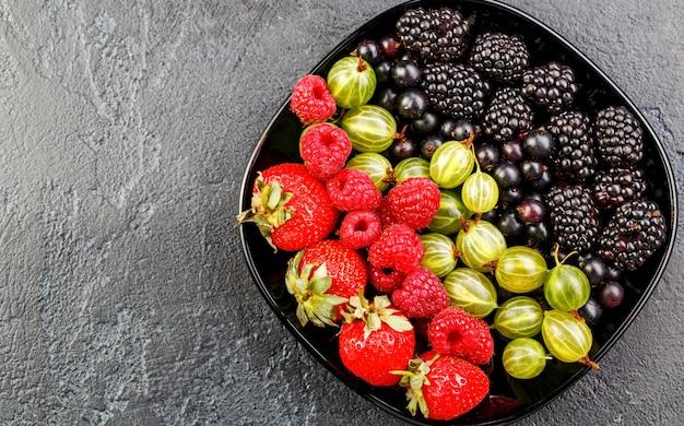 Zdjęcie na wierzchu jeżyn, truskawek, malin, agrestu, czarnej porzeczki na czarnej płycie na czarnej pustej powierzchni