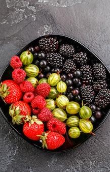 Zdjęcie na wierzchu jeżyn, truskawek, malin, agrestu, czarnej porzeczki na czarnej płycie na czarnym pustym tle