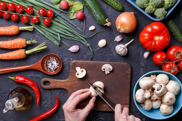 Zdjęcie na wierzchu świeżych warzyw, grzybów, deski do krojenia, oleju, noża, rąk kucharza
