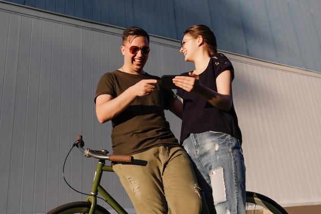 Zdjęcie na zewnątrz młodej atrakcyjnej pary, śmiejącej się razem podczas oglądania czegoś śmiesznego na telefonie komórkowym, spędzania czasu z przyjemnością, stania na rowerze.