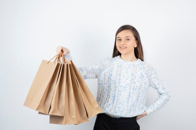 Zdjęcie nastolatka w sweter stojący i trzymając torby papierowe