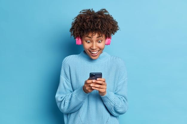 Zdjęcie nastolatki z afroamerykanki wpatruje się pod wrażeniem wyświetlacza smartfona, czyta niesamowite wiadomości, nosi różowe słuchawki stereo, słucha muzyki ubrana w dzianinowy sweter