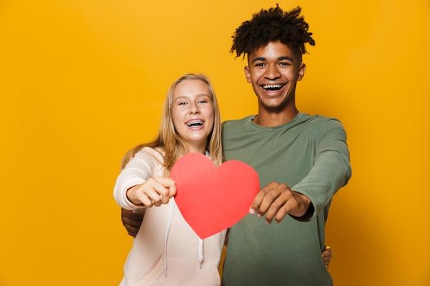 Zdjęcie nastoletnich przyjaciół mężczyzny i kobiety w wieku 16-18 lat trzymających papierowe serce, odizolowane na żółtym tle