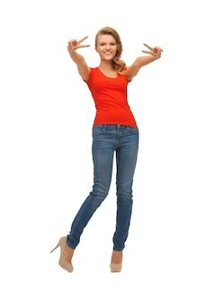Zdjęcie nastoletniej dziewczyny w czerwonej koszulce pokazującej znak zwycięstwa