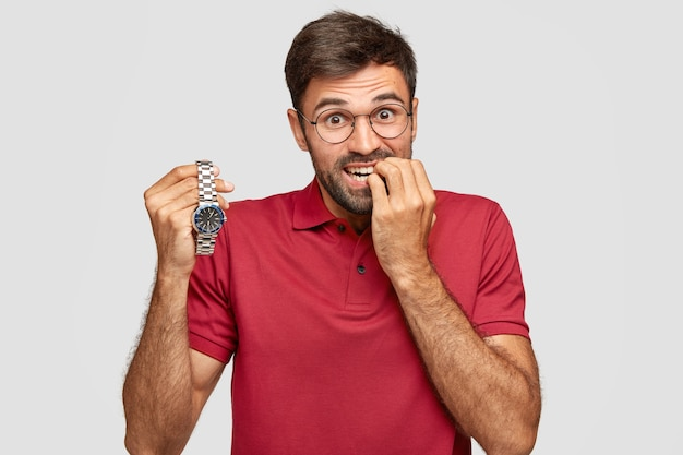 Zdjęcie nerwowego mężczyzny obgryza paznokcie, ma zaniepokojony wyraz