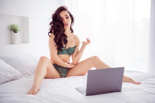 Zdjęcie niegrzecznej gorącej pięknej kobiety praca domowa kwarantanna online laptop czat rozłożone nogi boki pokazujące koronkowe majtki zdejmujące biustonosz nosić bikini siedzące białe lniane prześcieradła w pomieszczeniu