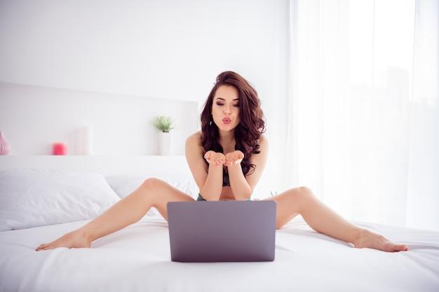 Zdjęcie niegrzecznej gorącej pięknej kobiety praca domowa kwarantanna online laptop czat wyślij powietrze buziaki ekran gotowy start pokaż rozłożone nogi boki nosić koronkowe bikini siedzący biały pościel prześcieradła w pomieszczeniu