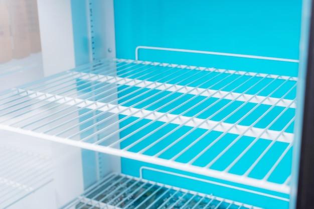 Zdjęcie niektórych czystych pustych półek stalowych białych lodówek.