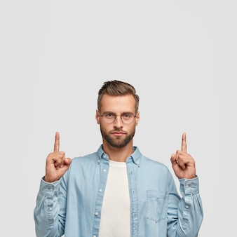 Zdjęcie nieogolonej hipsterki ubranej w casualową koszulę, skierowana dwoma palcami wskazującymi do góry.