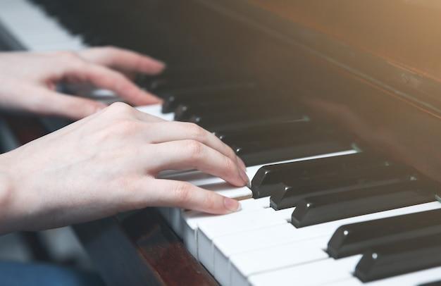 Zdjęcie nieostrości. kobieta gra na pianinie. ręce na klawiaturze. piękna muzyka. kreatywna dziewczyna na instrumencie muzycznym. sztuka klasyczna.