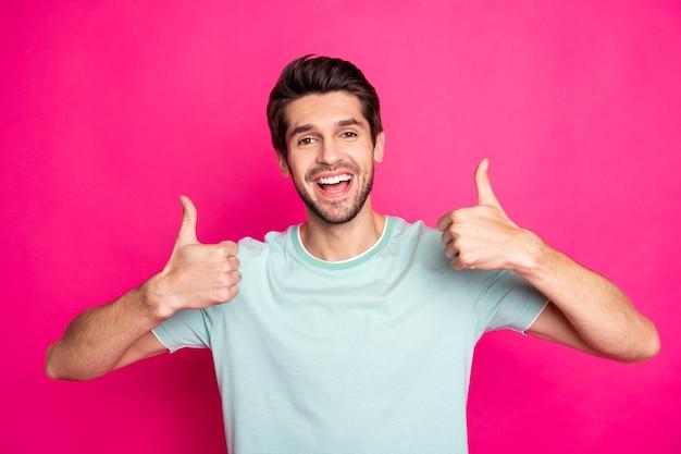 Zdjęcie niesamowitego faceta macho odsłaniającego idealne białe zęby, podnoszącego kciuki do góry, doradzającego dobrym dentystom nosić koszulkę na co dzień na białym tle żywy różowy kolor tła