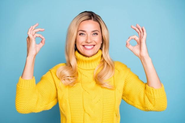 Zdjęcie niesamowitej blond pani przedstawiającej symbole okey wyrażające zgodę dobrą jakość produktu nosić dziany żółty sweter na białym tle niebieski kolor ściany
