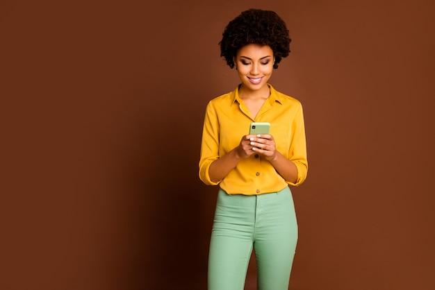 Zdjęcie niesamowitej ciemnej skóry falującej kobiety trzymającej telefon w rękach wpływowy piszący nowy post na blogu kreatywny motyw młodzieżowy nosić żółtą koszulę zielone spodnie na białym tle brązowy kolor