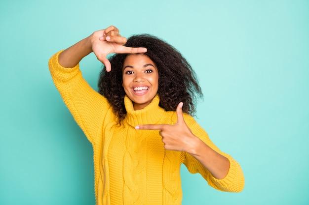 Zdjęcie niesamowitej ciemnoskórej pani robiącej wyimaginowaną ramkę robiącą zdjęcia nosić żółty sweter z dzianiny na białym tle niebieski turkusowy kolor ściany