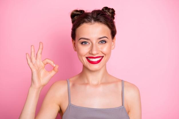 Zdjęcie niesamowitej dziewczyny ładne bułeczki czerwone usta pokazujące w porządku symbol wyrażający zgodę dobra robota nosić dorywczo szary podkoszulek izolowany różowy kolor