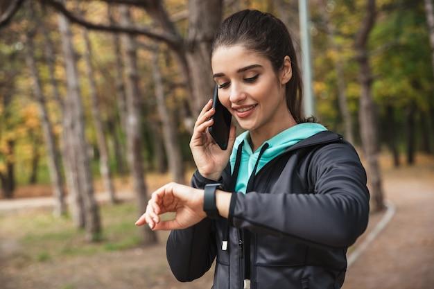 Zdjęcie niesamowitej młodej kobiety dość fitness na świeżym powietrzu w parku patrząc na zegarek zegar rozmawia przez telefon komórkowy.