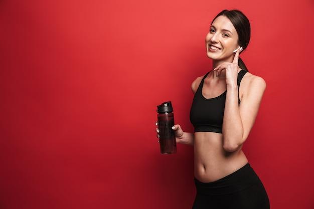 Zdjęcie niesamowitej młodej pięknej kobiety fitness pozuje na białym tle nad czerwoną ścianą ściany lodowisko wody słuchania muzyki ze słuchawkami.