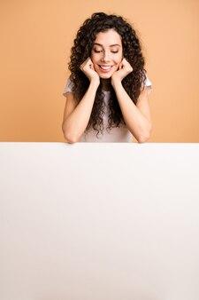 Zdjęcie niesamowitej pani, która z zainteresowaniem patrzy na pusty baner rabatowy pochylony duży biały plakat na białym, codziennym ubraniu na białym tle beżowym pastelowym kolorze