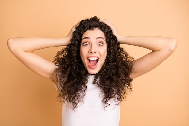 Zdjęcie niesamowitej pani trzymającej ręce na głowie z otwartymi ustami słuchając świetnej reklamy sprzedaży zakupy nosić biały strój na co dzień na białym tle beżowy pastelowy kolor tła