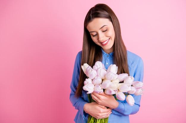 Zdjęcie niesamowitej pani trzymającej w rękach duży bukiet świeżych białych tulipanów